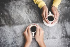 Top view with copy space. Couple in love holding hands with coffee love on table, stock image