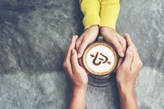 Top view with copy space. Couple in love holding hands with coffee love on table, vintage tone royalty free stock photo