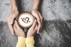 Top view with copy space. Couple in love holding hands with coffee love on table, vintage tone. stock images