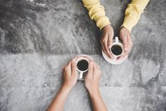 Top view with copy space. Couple in love holding hands with coffee love on table, vintage tone. stock photo