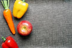 Top view with copy space. Fresh colorful Vegetables consists of orange carrot, red apple, Yellow and red bell pepper. On gray textured background, ready for Stock Photos