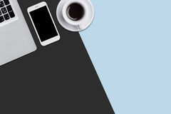 Top view with copy space of laptop, cell phone and cup of coffee or tea. Modern gadgets lying on black and blue background. View f. Rom above. Office desk for royalty free illustration