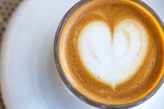 Top view of cortado coffee in a glass with the foam in shape of heart.  Royalty Free Stock Image