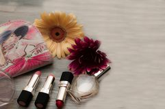 Top view of cosmetic bag consist of makeup brush, lipstick, brush on, scissors, mascara, eyelash curler on background - vintage fi. Lter royalty free stock image