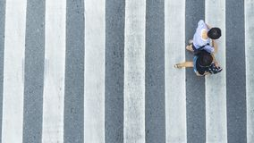 The top view of couple people walk across the pedestrian crosswa. Lk in white and grey pattern Royalty Free Stock Photos