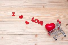 Top view couple red heart shape with mini shopping cart on wooden table. love, shopping and Valentine Day stock photography