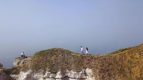Top view of couple walking along cliff path. Action. Young couple in love walks along narrow path in hot summer on stock video footage