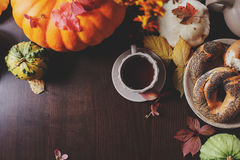 Top view of cozy autumn breakfast at country house with tea, bagel and seasonal decorations Stock Photo