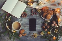 Top view of cozy Christmas and winter setting with homemade cookies, coffee, nuts, weekly planner and New Year decorations Royalty Free Stock Images