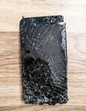 Top view cracked broken mobile screen glass on the wooden floor.  royalty free stock photography