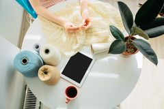 Top view of craftswoman`s hands knitting something with crochet in cozy workplace at home interior. Female working with tender royalty free stock images