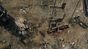 Top view of crane with cement tank rising up on building site. Polluted, brown ground with rubbish, wood planks, send. Workers in black T-shirt, white helmet stock footage