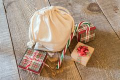 Top view of cream canvas santa sack with gifts on rustic wooden Royalty Free Stock Photo