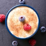 Top view on creamy dessert with cinnamon and summer berries. Square photo with top view on creamy dessert with cinnamon sugar on surface. Summer berries as Royalty Free Stock Images