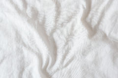 Top view of creased / wrinkles on a white unmade / messy bed sheet. Royalty Free Stock Images