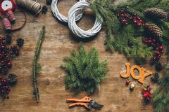 Creation of Christmas wreaths. Top view of creation of Christmas wreaths with fir branches and pine cones on wooden tabletop with word Joy Stock Photos