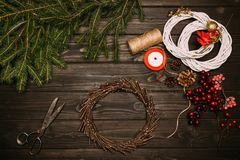 Wreaths with Christmas decorations. Top view of creation of wreaths with fir, twine and Christmas decorations on wooden tabletop Royalty Free Stock Image