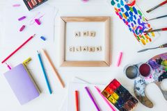 Top view creative art class concept. Canvas in frame with lettering inside and many colorful paintiing materials on the white. Wooden background. Drawing lesson royalty free stock photo