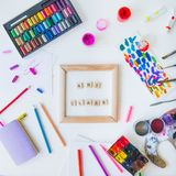 Top view creative art class concept. Canvas in frame with lettering inside and many colorful paintiing materials on white wooden. Background. Drawing lesson for stock images