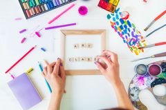 Top view creative art class concept. Female Hands add letter to inscription on Canvas with many colorful paintiing materials on. White wooden background stock photos