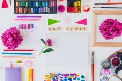 Top view creative artist workplace. Blank Canvas, Art class lettering on wooden blocks and various colorful painting materials and. Flowers on white background stock photo