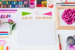 Top view creative artist workplace. Blank Canvas, Art class lettering on wooden blocks and various colorful painting materials and. Flowers on white background royalty free stock photography