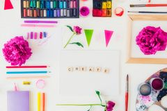 Top view creative artist workplace. Blank canvas with Create word lettering, variety of painting supplies and peony flowers. Drawing, inspiration, craft royalty free stock photos