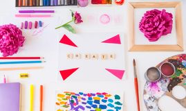 Top view creative artist workplace. Blank canvas with Create word lettering, variety of painting supplies and peony flowers. Drawing, inspiration, craft royalty free stock images
