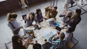 Top view of creative business team working at modern office. Colleagues talking, smiling, high five with each other.