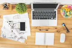Workspace with empty gadgets and sketch. Top view of creative designer workspace with empty gadgets, supplies and architectural sketch. Workplace and engineering Stock Photo