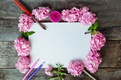 Top view Creative layout made of pink wisteria flowers, canvas blank, brushes, fuchsia color gouache paint, color pencils on the o. Ld wooden rustic table. Flat royalty free stock images
