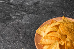 A top view of crispy cheese nachos on a a light wooden round plate. Delicious corn chips on a gray stone background Stock Photography