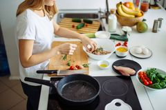 Woman making kebabs from meat and vegetable on chopping board in kitchen. Top view of cropped female body sticking chicken bits, pickled in rosmary and oil on Royalty Free Stock Image