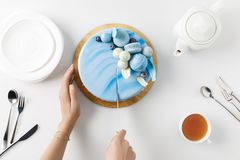 Top view of cropped hands slicing cake on chopping board. Isolated on white stock images