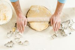 top view of cropped male hands rolling dough on table stock photo