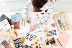 Top view cropped photo of young woman fashion illustrator drawing. Top view cropped photo of young woman fashion illustrator sitting at the table and drawing stock photography