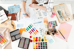 Top view cropped photo of young woman fashion illustrator. Sitting at the table and drawing royalty free stock photos