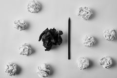 Top view of crumpled black and white papers with pencil. On white surface stock photos