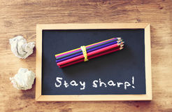 Top view of crumpled paper and pencils stack over blackboard with the phrase stay sharp. Top view of crumpled paper and pencils stack over blackboard with the Royalty Free Stock Photos