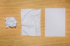 Top view of crumpled papers and blank white paper on wooden. Table stock photography