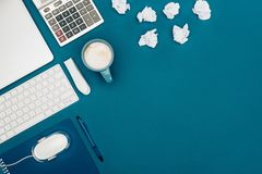 Top view of crumpled papers, calculator and digital devices. On blue royalty free stock photo