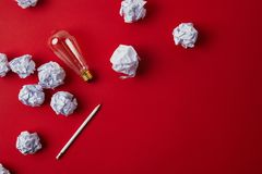 Top view of crumpled papers with light bulb and pencil. On red surface stock photo