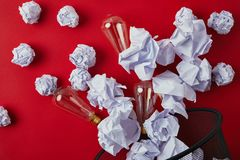 Top view of crumpled papers with vintage incandescent lamps spilled from trash bin. On red tabletop stock photo