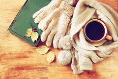 Top view of Cup of black coffee with autumn leaves, a warm scarf and old book on wooden background. filreted image Stock Photo