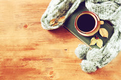 Top view of Cup of black coffee with autumn leaves, a warm scarf and old book on wooden background. filreted image Stock Image