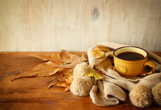 Top view of Cup of black coffee with autumn leaves, a warm scarf on wooden background. filreted image. Stock Photo