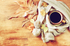 Top view of Cup of black coffee with autumn leaves, a warm scarf on wooden background. filreted image. Stock Photos