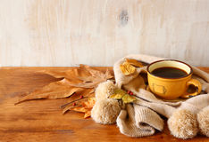 Top view of Cup of black coffee with autumn leaves, a warm scarf on wooden background. filreted image Stock Photos