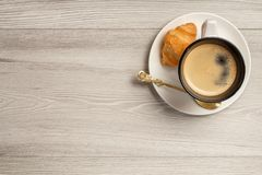Top view of cup of black coffee with fresh croissant and spoon o. N saucer with copy space on grey wooden background Royalty Free Stock Photography
