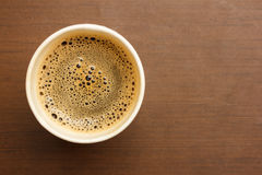 Top view of a cup of black coffee on wooden table. Top view of a paper cup of black coffee on wooden table stock images